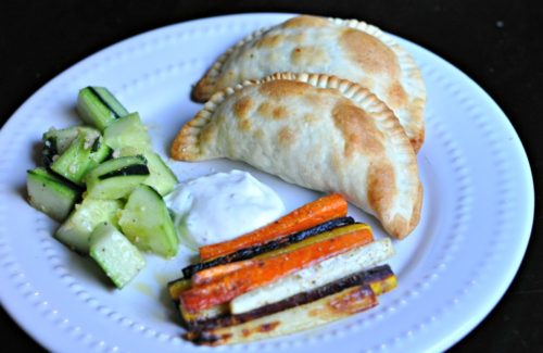 Empanadas, cucumber salad and roasted carrots from Blue Apron on a white plate