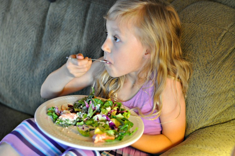 Kaylee eating a salmon salad from our Blue Apron Meal Kit while sitting on the couch