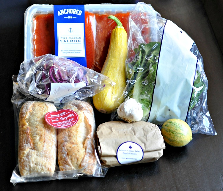 Fresh salmon, squash, bread rolls, lettuce and other ingredients for salmon salad from Blue Apron meal kit on dark wood table