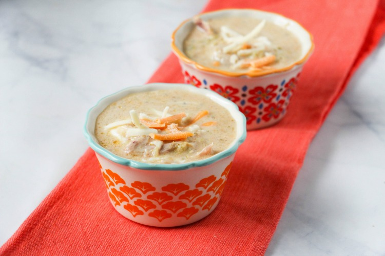 Two bowls of Instant Pot Broccoli Cheese Soup with chicken on an orange runner
