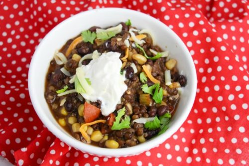 Bowl of Instant Pot Vegetarian Chili in a white bowl on a red and white polka dot napkin