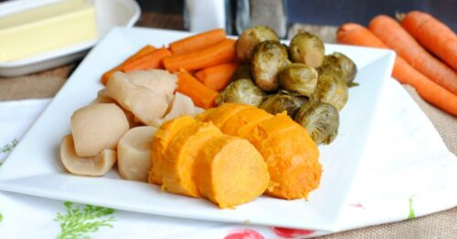 White plate of vegetables on table with raw carrots, butter, salt and pepper