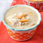 Bowl of Instant Pot Broccoli Cheese Soup with Chicken on an orange runner ready to eat