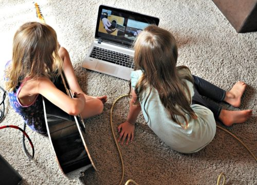 Zoe and Kaylee taking guitar lessons from fender on a laptop while sitting on the carpet
