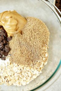 Peanut butter energy bites ingredients in glass mixing bowl