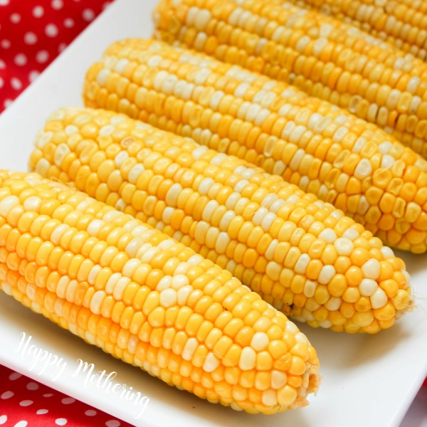 Close up of five ears of corn cooked in an Instant Pot laid out on a white serving platter