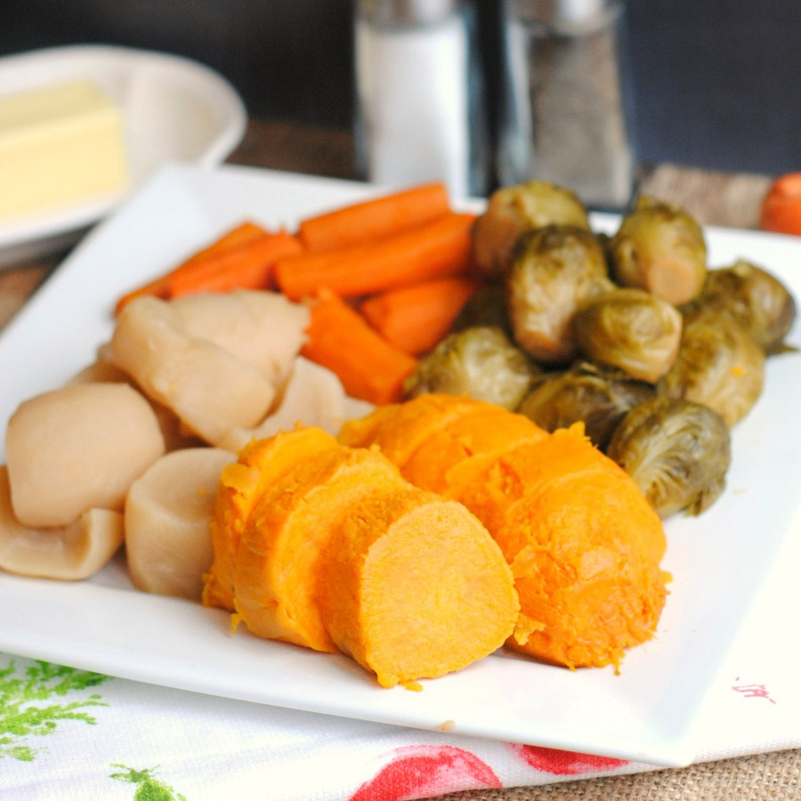 Square white plate of sweet potatoes, turnips, carrots and brussels sprouts that were cooked in an Instant Pot and served with butter, salt and pepper
