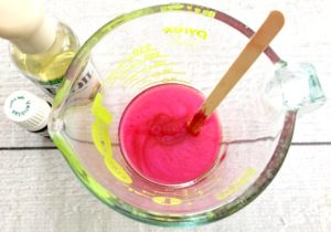 Pinkish red mica stirred into the melted lip balm mixture in a glass measuring cup