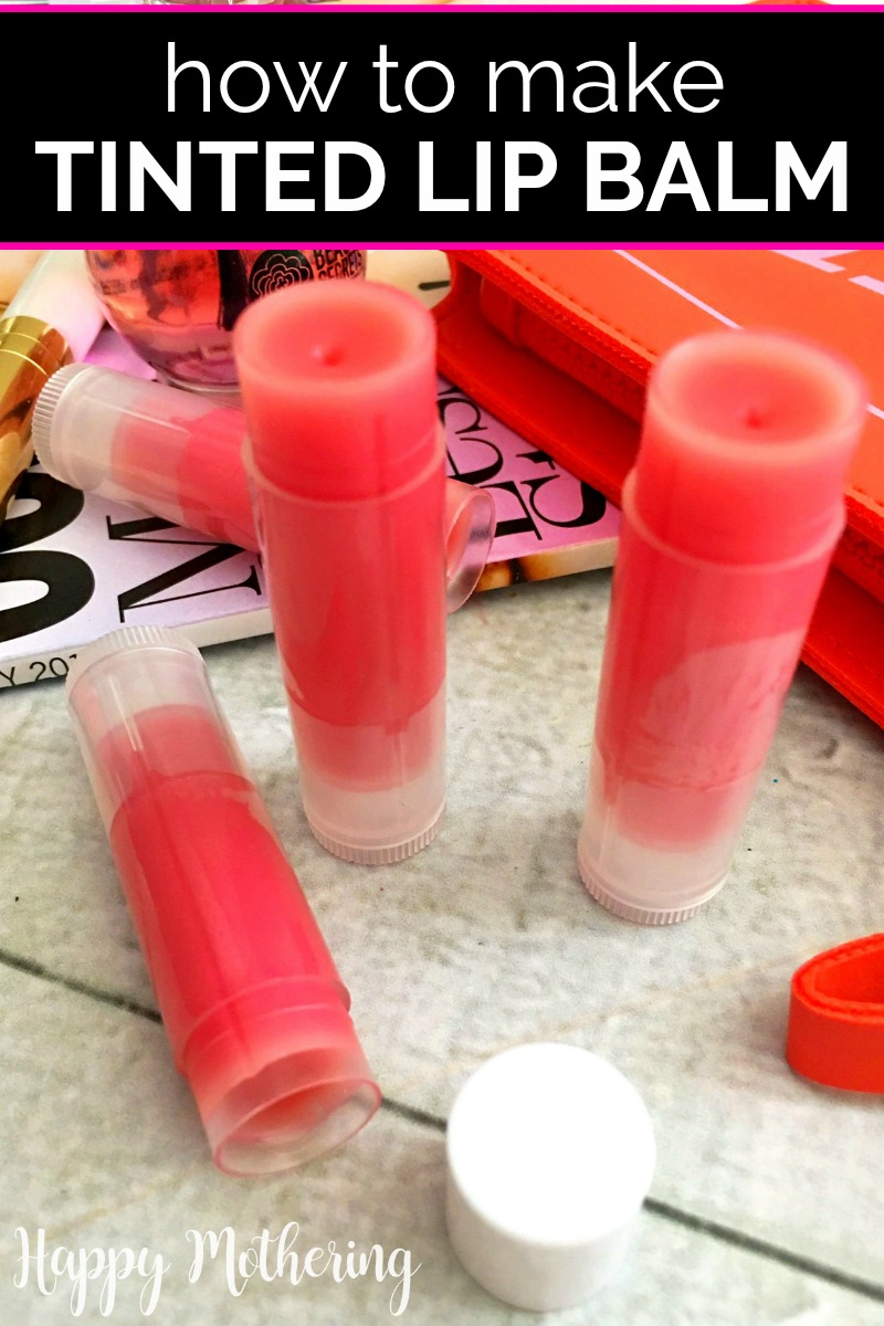 Four tubes of mica tinted lip balm on a white wood table with a pink clutch and magazine