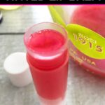Single chapstick tube filled with melted pink tinted lip balm on a white wood table with the cap and a measuring cup of more lip balm mixture next to it