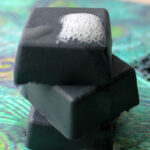 Close up of 3 stacked and lathered charcoal soap bar squares