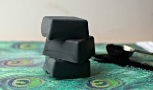 3 bars of activated charcoal face wash soap bars stacked on top of each other on a green placemat