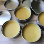 Four balm tins open with lids on wood table.