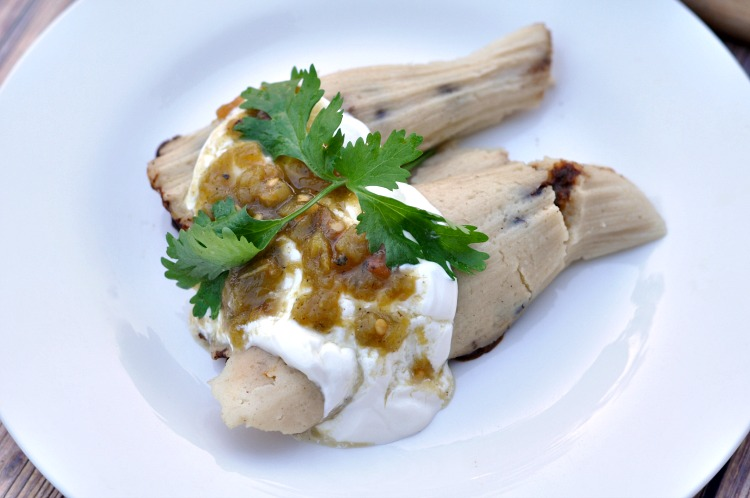 Overhead view of two tamales on a white plate