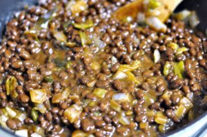 Black beans and hatch chiles added to pan of sauteed onions