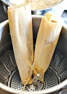 Tamales placed open side up in steamer pan
