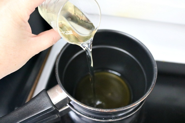 Adding oil to beeswax in double boiler