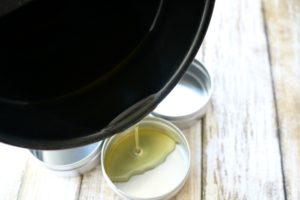 Pouring menstrual cram pain relief salve into metal tins
