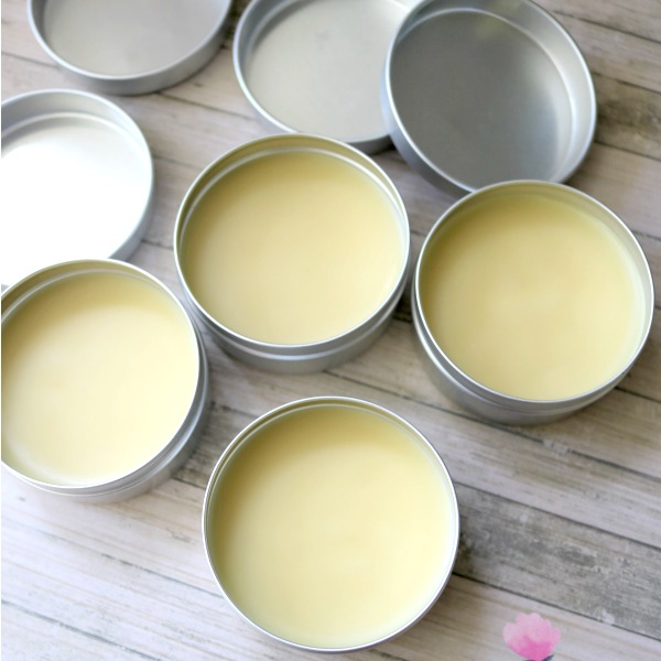 Square image of four tins of menstrual pain relief salve