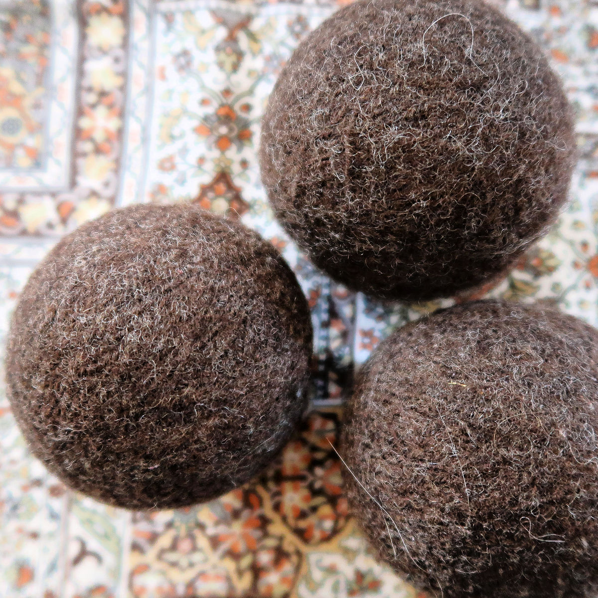 3 wool dryer balls on a patterned tablecloth