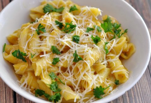 Butternut squash sauce over gluten free pasta topped with parmesan and parsley in a white bowl