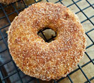 Gluten free snickerdoodle pumpkin donut on a cooling rack