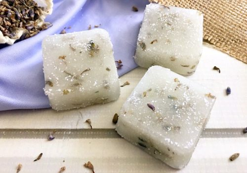 Three homemade lavender sugar scrub cubes on a white table with dried lavender buds