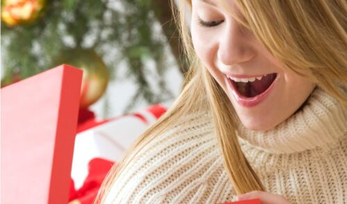 Surprised teen girl looking inside gift package