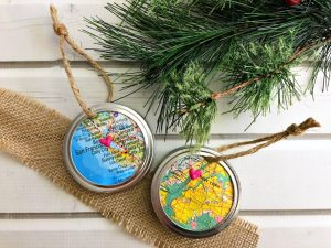 Two Mason Jar Ring Map Ornaments on a white table with Christmas tree branch