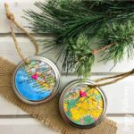 Two Mason Jar Ring Map ornaments with burlap and artificial Christmas tree branches on a vintage white wood table