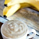 White teacup filled with homemade banana oatmeal face mask on a brown place mat on a wood table with two whole bananas behind the cup