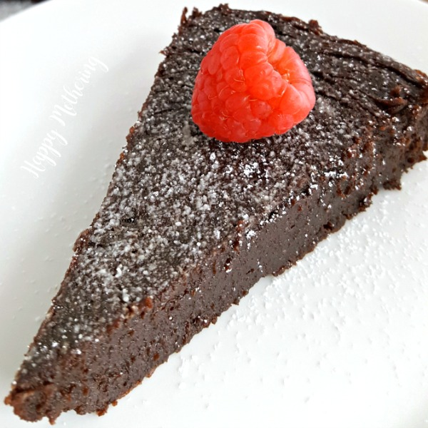 Slice of gluten free flourless chocolate torte topped with a raspberry