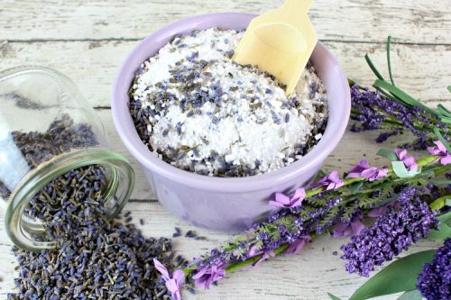 Lavender bath salts in a lavender bowl with a wood spoon