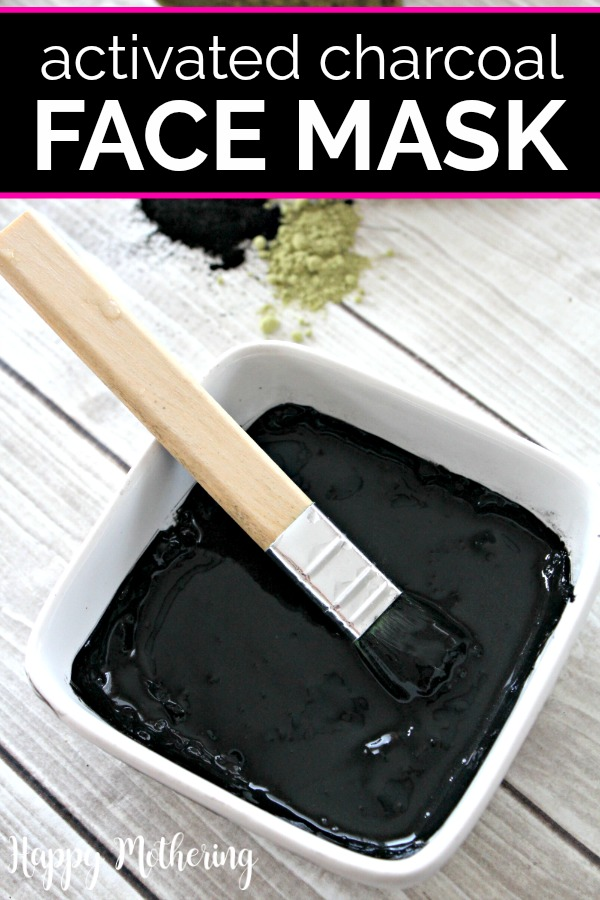 Activated charcoal face mask in white bowl with paintbrush