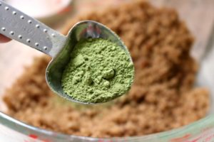 Matcha green tea powder being added to a glass bowl with brown sugar and coconut oil.