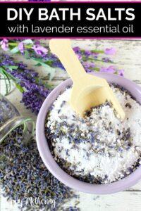 Overhead view of lavender bowl of bath salts with wood spoon and dried lavender spilled on a white wood table