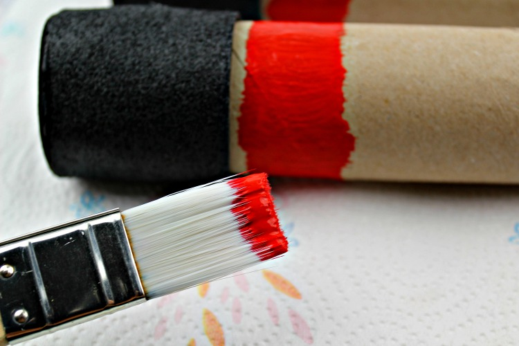 Toilet paper tube painted with a stripe of red.