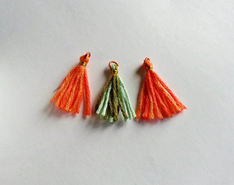 Two orange and one green tassel