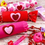 Three treat poppers (one red, one pink and one white with pink hearts) on a wood table with some of the treats you can find inside like bead necklaces, rubber duckies, candy and a pen