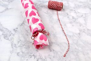 Tissue paper over a toilet paper tube tied off at one end with baker's twine.