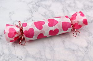 Toilet paper tube filled with candy and toys, covered in heart print tissue paper and tied closed with baker's twine.