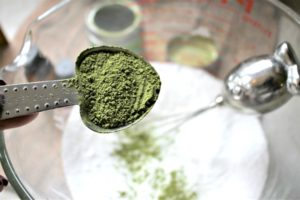 Matcha green tea being added to baking soda and epsom salts in a bowl