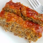 Two slices of meatloaf on a white plate with a fork.
