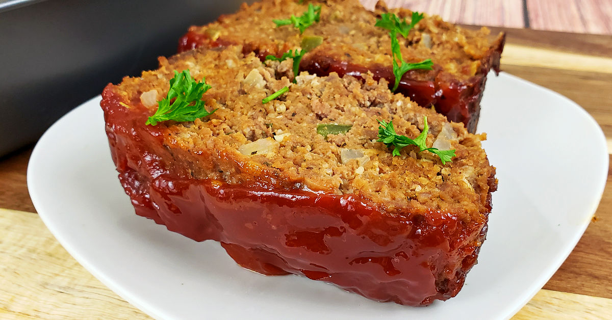 Two slices of gluten free meatloaf on a square white plate, topped with chopped parsely.
