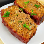 Close up of two slices of gluten free meatloaf topped with chopped parsley on a white plate.