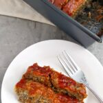 Overhead view of two slices of gluten free meatloaf on a white plate with a fork next to the loaf pan of the remaining meatloaf
