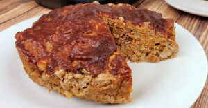 Instant Pot meatloaf resting on white serving plate with one slice removed.