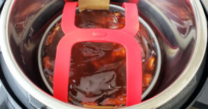 Meatloaf mixture in cake pan lowered into Instant Pot inner pan with red silicone sling.