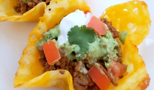 Close up of a keto taco shell on a white plate topped with ground beef, tomatoes, guacamole sour cream and cilantro