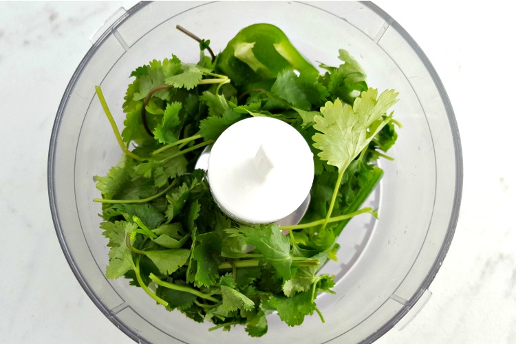 Ingredients in a food processor to make cilantro jalepeno sauce